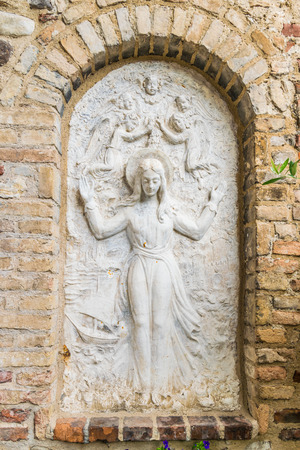 bas relief: Bas relief surrounded by brick wall representing the Virgin Mary surrounded by angels.
