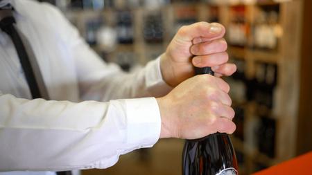 sommelier: Sommelier uncorks a bottle of sparkling wine in a wine shop. Stock Photo