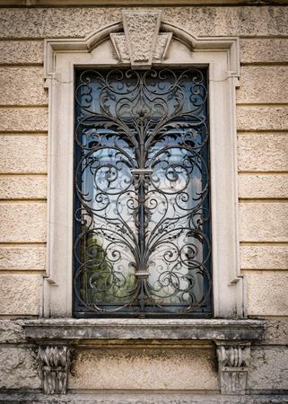 medieval blacksmith: Window of an ancient Italian villa with artistic iron grill handmade.