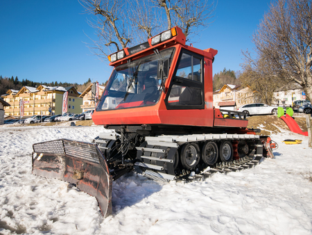 snow grooming machine: Trento, Italy - February 21, 2016: Red snowcat parked at the end of a ski slope.