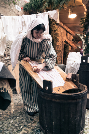launder: Riva del Garda, Italy - December 26, 2015: Laundress washes clothes with soap and water on a wooden board. Editorial