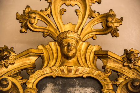 mirror frame: Detail of a carved gilded frame of an antique mirror.
