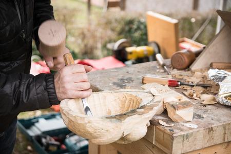 Carpenter carves a wooden carnival mask.