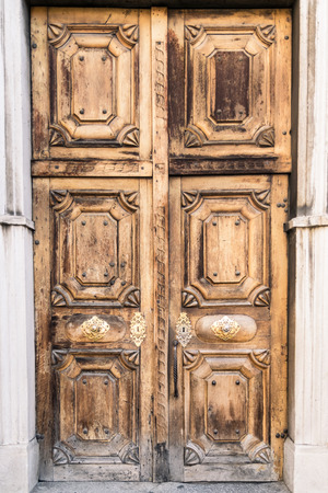 archways: Entrance of a medieval cathedral with carved wooden door. Stock Photo