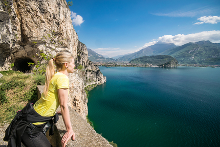 Young sporty woman admire the panorama from the Ponale trail in Riva del Garda, Italy.