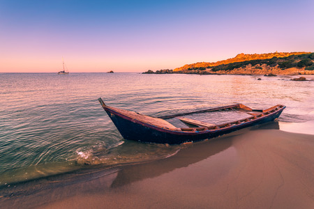 Old wooden boat wrecked on a sandy beach. Stock Photo