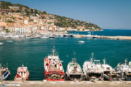 Porto Santo Stefano, Italy - June 24, 2017: Harbor seafront and village skyline, italian travel destination. Monte Argentario, Tuscany, Italy. Editorial
