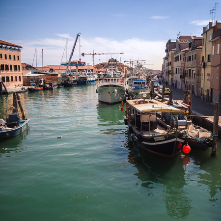 Chioggia, Italy - April 30, 2017: Fishing boats moored in a canal in Chioggia, Venetian Lagoon, Italy. Editorial