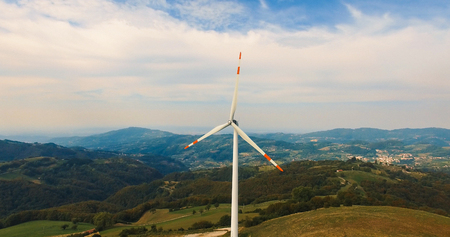 Single wind turbine on the green hill. Stock Photo