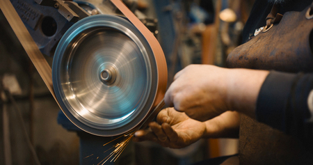 Craftsman uses a belt sander in a mechanical workshop.