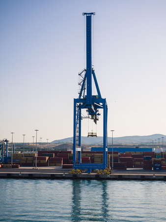 livorno: Livorno, Italy - August 27, 2017: Shipping industrial trade port. Crane bridge and import export container at shipping port harbor.