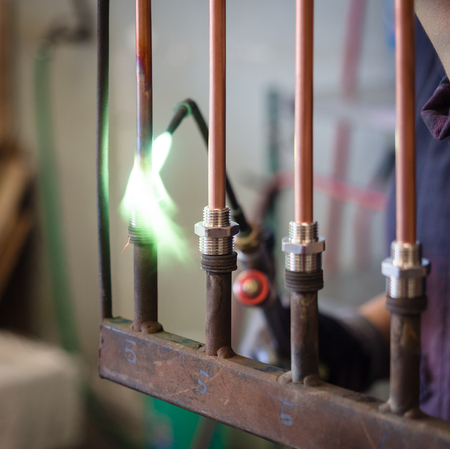 Detail of soldering of brass fittings on copper pipe.
