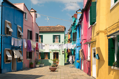 Colorful houses by canal in Burano, Venice, Italy. Burano is an island in the Venetian Lagoon and is known for its lace work and brightly colored homes. Banco de Imagens