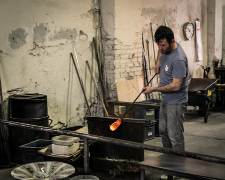 Murano island, Italy - April 23, 2017: Glassblowing artisan at work in a crystal glass workshop in Murano island, Venice. Murano glassmakers use the same tools as their ancestors have thousands of years ago. Editorial