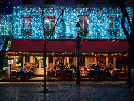 Montmartre, Paris - January 7, 2018: Night view of the famous square of artists and typical restaurants with outdoor tables that surround it.