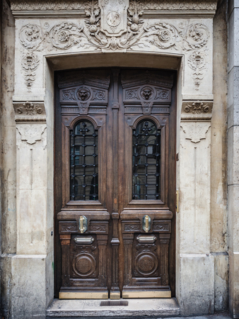 Antique inlaid wooden door with carved stone structure in an ancient palace in Paris.