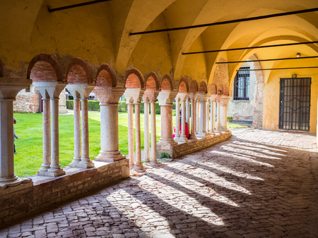 Porch with white stone columns in the courtyard of a Benedictine abbey. Archivio Fotografico