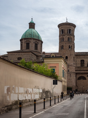Ravenna, Italy - May 1, 2018: External view with the early Christian bell tower, the baroque cathedral and the neoclassical dome.