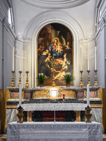 Urbino, Italy - April 30, 2018: Altar dedicated to the Virgin Mary with painting depicting the virgin with child Jesus surrounded by angels and saints.