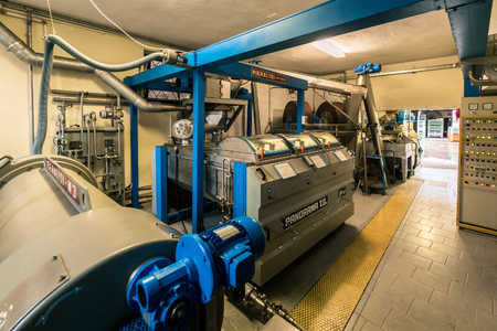Verona, Italy - November 25, 2016: Machines for processing olive paste in a modern Italian oil mill.