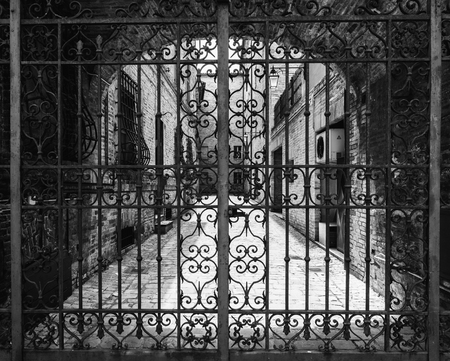 Hand-worked wrought iron gate with internal courtyard of an old Italian building.