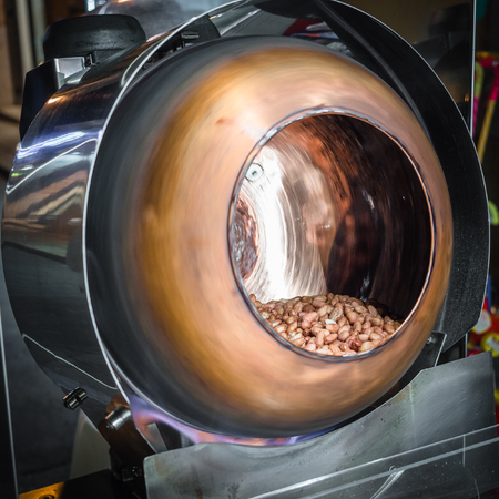 Revolving copper pot used to caramelize peanuts. Reklamní fotografie