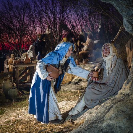 Villaga, Italy - December 30, 2017: Woman helps a leprous beggar during the representation of the Nativity that traditionally takes place every year.