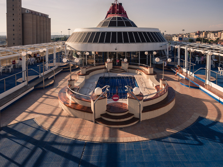 Cagliari, Italy - August 26, 2017: Upper deck of a ferry with swimming pool at sunset. Standard-Bild - 118809991