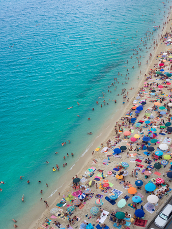 Tropea, Italy - August 21, 2018: Beach with crystalline sea crowded with swimmers. Top view.