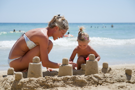 Sardinia, Italy - August 15, 2014: Mom and daughter building a castle of sand on the beach near the crystal clear sea. Editorial