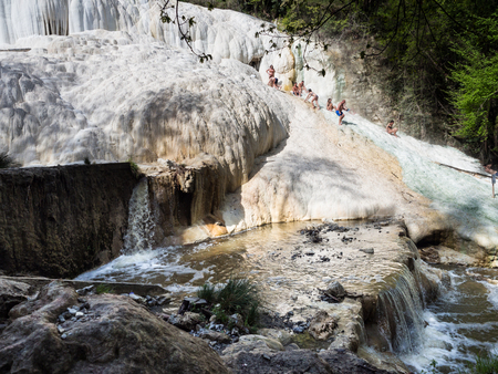 Bagni San Filippo, Italy - April 24, 2019: People rest on the thermal salt waterfalls of the mineral springs of Bagni San Filippo on a sunny day.