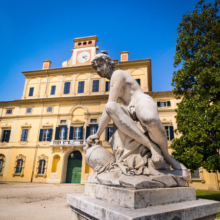 Parma, Italy - April 8, 2018: Classical style stone statue in front of the garden palace inside the ducal park of Parma, Italy.