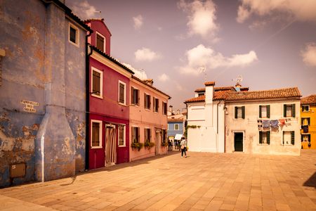 Burano, Italy - April 23, 2017: Colorful houses by canal in Burano, Venice, Italy. Burano is an island in the Venetian Lagoon and is known for its lace work and brightly colored homes.