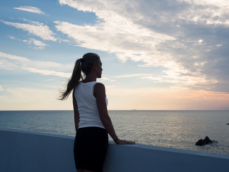 Tropea, Italy - August 20, 2018: Blonde woman watching the sunset from a terrace overlooking the sea.