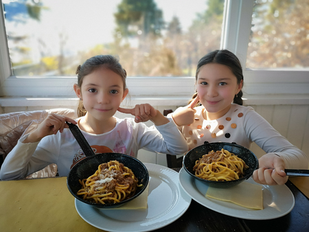Verona, Italy - March 17, 2019: Little girls eat spaghetti with meat sauce served directly in the pan.