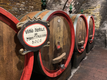 Montepulciano, Italy - April 23, 2019: Oak barrels in an old Italian underground wine cellar.