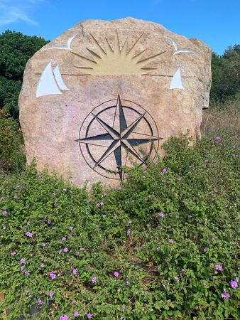 Wind rose painted on a rock surrounded by green bushes. Фото со стока