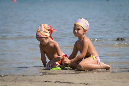 Lecce, Italy - August 4, 2015: Two little girls playing with sand near the crystal clear sea of south Italy.