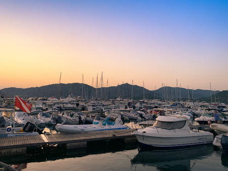Villasimius, Italy - August 12, 2019: Sunset on the marina of Villasimius. Recreational boats are still in calm water.