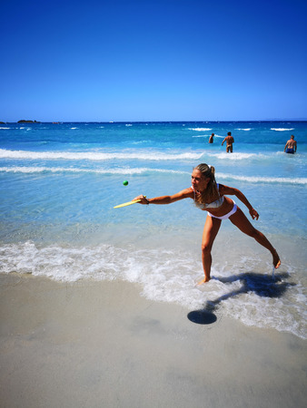 Villasimius, Italy - August 16, 2019: Woman plays beach tennis on the shore of the blue Sardinian sea.