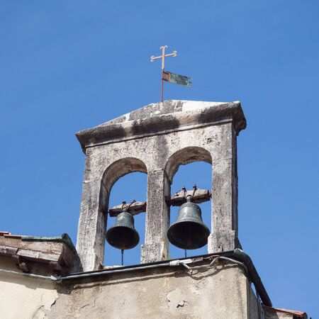 Detail of the bell tower of an ancient small Catholic church.