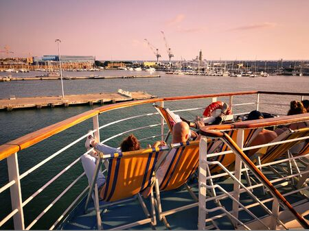Passengers of a ferry relax on deck chairs while going on holiday.