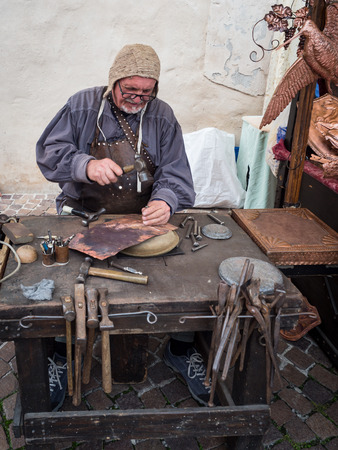 Garda, Italy - October 6, 2019: Detail of a craftsman engraves a copper plate with a hammer and chisel. Redakční