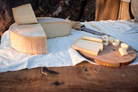 Matured cheese on table and wooden cutting board.