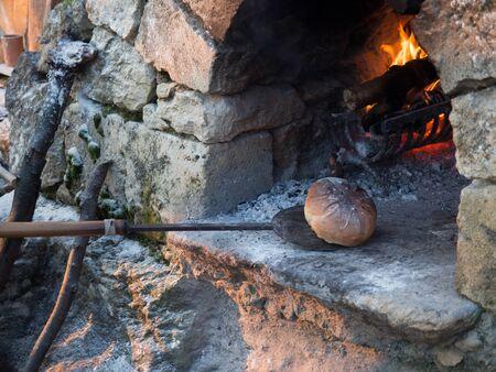 Baking bread in a wood oven built using stones. 版權商用圖片