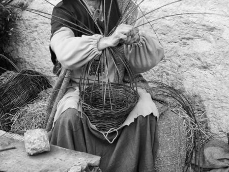Woman weaves baskets by hand in a rural area market.