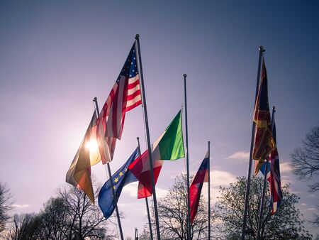 Flags of various states of the world fly together at sunset.