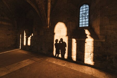 Shadow of parents with small child inside an ancient medieval stone cathedral.