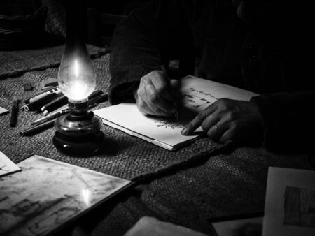 A man draws in a dark and poor room in the light of an oil lantern. 版權商用圖片