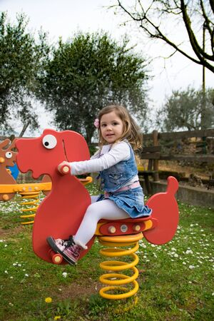 Verona, Italy - March 29, 2015: Child plays on a read spring dog in a playground.